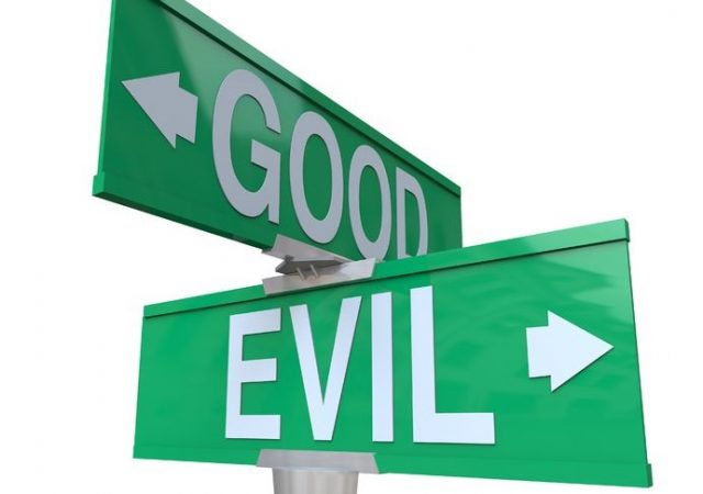 a green two-way street sign pointing to good or evil,