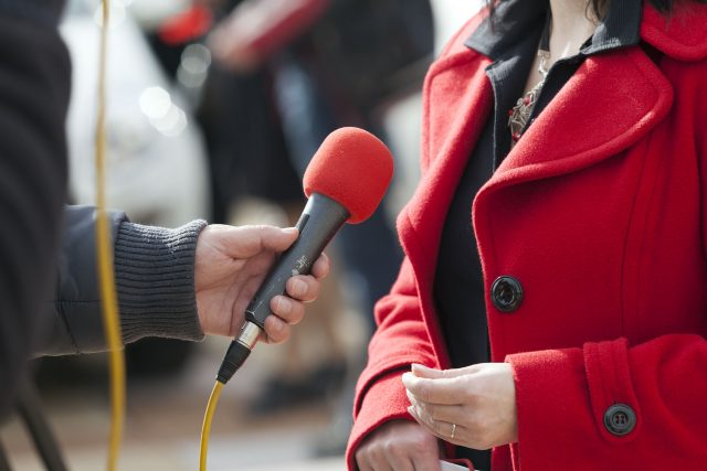 Ask An Expert: Aimee Hobby Rhodes - Journalist with a Microphone Interviewing Woman in Red Coat